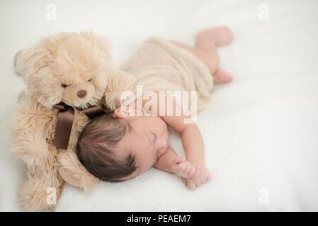 Carino neonato dorme su una coperta con un giocattolo orsacchiotto - happy i momenti in famiglia Foto Stock