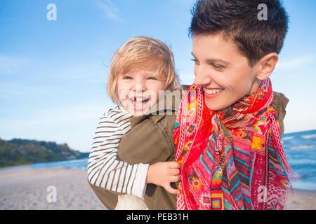 Ritratto di gruppo di sorridere white Caucasian madre e figlia bambina, piggy back riding, giocando in esecuzione sul mare oceano spiaggia al tramonto all'aperto, hap Foto Stock