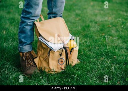 Ritagliato colpo di uomo in piedi su erba verde con zaino Foto Stock