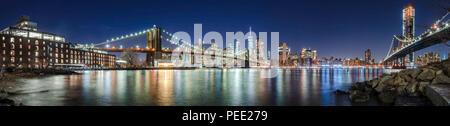 I grattacieli di Manhattan, il Ponte di Brooklyn e il Manhattan Bridge in serata con la East River (panoramico). La città di New York Foto Stock