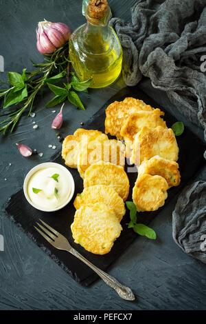 Vegano frittelle vegetali su uno sfondo di ardesia tagliere. Vegetariano fritto cotolette o frittelle. Il concetto di fast food. Copia dello spazio. Foto Stock
