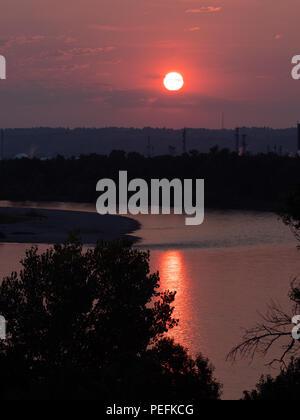 Rosso, rosa e viola alba con il sole sopra una zona urbana. Inquinamento da fumo da incendi boschivi fa un drammatico sunrise. Foto Stock