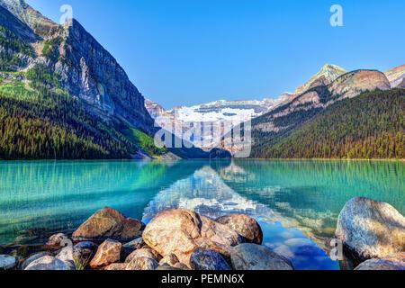 Lake Louise a Banff National Park con il suo alimentati da ghiacciai laghi turchesi e il Monte Victoria Glacier in background. Visitatori paddling canoe rosso in Foto Stock