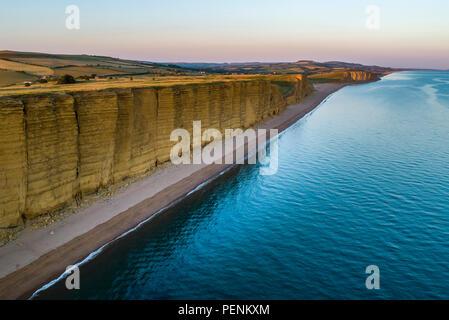 Immagine drone di caldo della spiaggia e scogliere in West Bay Dorset durante il crepuscolo. Foto Stock