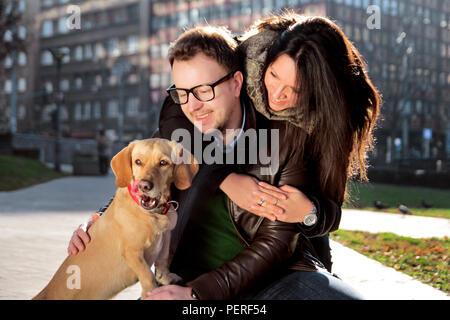 Abbracciando la ragazza giovane uomo mentre lui accovacciato e coccolare il cane e godono tutte di una bella giornata nel parco. Giovane coppia felice con il cane godere. Foto Stock