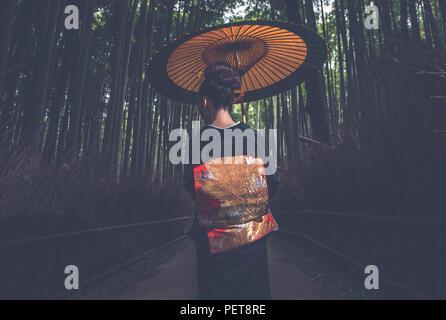 Bella giapponese donna senior passeggiate nella foresta di bamboo Foto Stock