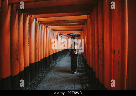 Bella giapponese donna senior a piedi nei Fushimi Inari shrine in Kyoto Foto Stock