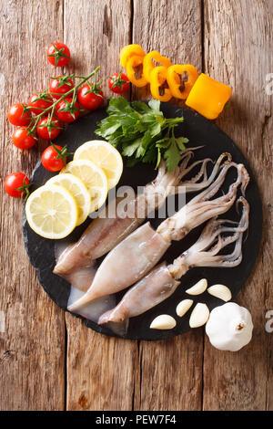 Materie calamari freschi close-up e vegetali per la cottura su una scheda di ardesia su un tavolo. Verticale in alto vista da sopra Foto Stock