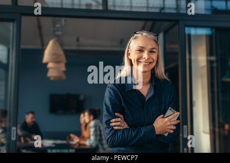 Ritratto di sorridere senior woman standing in office porta con le braccia incrociate. Bellissima femmina executive in ufficio con le persone che incontro in backgro Foto Stock