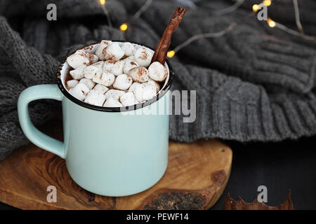 Blu e smalto nero tazza di cioccolata calda con marshmallows e corteccia di cannella. Estrema profondità di campo con il focus sulla bevanda. Foto Stock