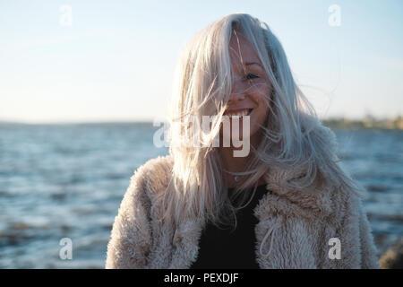 Stile di vita Ritratto di giovane donna bionda nella giornata di vento in mare Foto Stock