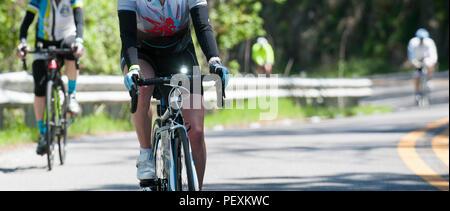 Persone escursioni in bicicletta lungo la strada Foto Stock