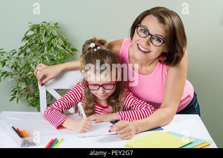 La mamma aiuta il bambino a scrivere. Ragazza 6, 7 anni con gli occhiali seduto al tavolo e la scrittura nel notebook. Foto Stock