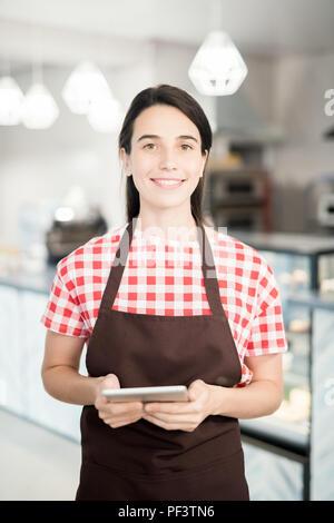 Giovane cameriera in posa Cafe Foto Stock