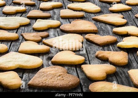 A forma di cuore i cookie su un vecchio tavolo in legno Foto Stock