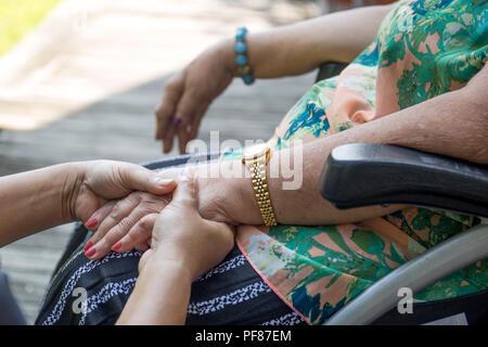 Donna anziana in carrozzina tenendo le mani con il caregiver in giardino Foto Stock