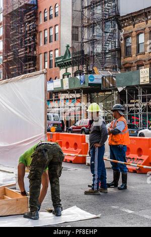 La città di New York, Stati Uniti d'America - 20 Giugno 2018: Tre operai a lavorare sul sito in costruzione in Street a New York City Foto Stock