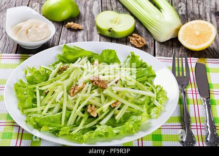 Studio macro di Insalata Waldorf su un piatto bianco su un tovagliolo da tavola con coltello e forchetta, autentica ricetta, metà del limone e apple, sedano e mayo in un Foto Stock