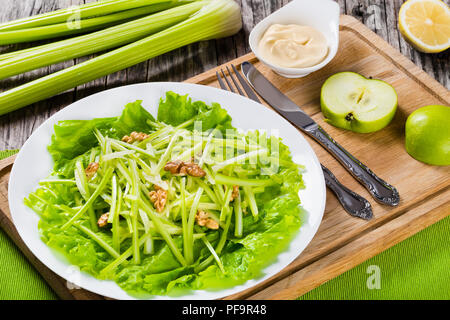 Studio macro di fresca Insalata Waldorf con noci, di mela verde e sedano, autentica ricetta, la metà di un limone, il sedano e la Mayo in una salsiera su un legno Foto Stock