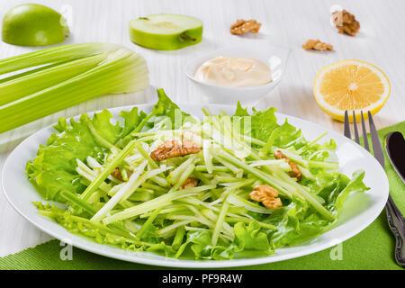 Studio macro di Insalata Waldorf, autentica ricetta, la metà di un limone e di Apple, il sedano e la Mayo in una salsiera su un bianco tavolo di legno, vista da sopra Foto Stock