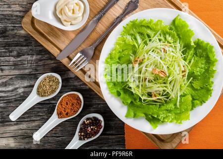 Fresca Insalata Waldorf con noci, di mela verde e sedano, autentica ricetta, la metà di un limone, il sedano e la Mayo in una salsiera su una tavola di legno, visualizzare fro Foto Stock