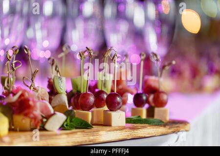 Solenne felice anno nuovo banchetto. Lotto di bicchieri di champagne o vino sul tavolo nel ristorante. tavolo da buffet con un sacco di deliziosi spuntini. crostini e bruschette, e un po' di dessert sul piatto di legno board Foto Stock