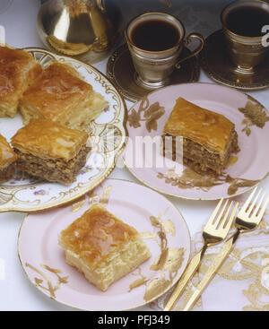 Pezzi di più livelli di torta di mele servita su piatti, caffè servito in bicchieri d'argento Foto Stock