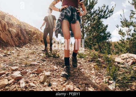 Explorer giovane a camminare in una foresta. Donna che cammina su un sentiero roccioso con il suo partner dopo di lei in una giornata di sole. Foto Stock