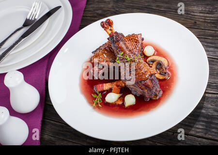 Porzione di Coq au Vin o pollo brasati con vino, lardons, i funghi e le erbe, autentica ricetta francese, vista da sopra, close-up Foto Stock