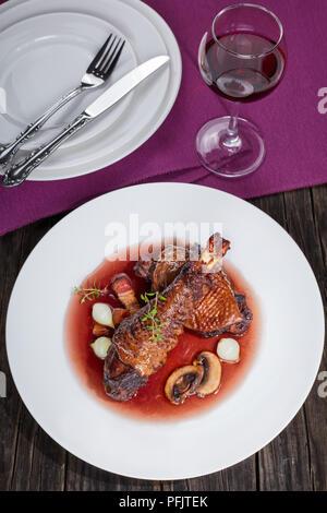 Porzione di spezzatino di pollo - coscia e la coscia brasati con vino, lardons, i funghi e le erbe serviti sulla piastra con un bicchiere di vino rosso, autentico francese Foto Stock