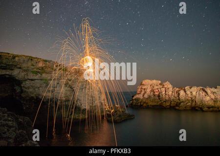 La filatura della lana di acciaio fuochi d'artificio su rocce e mare Foto Stock