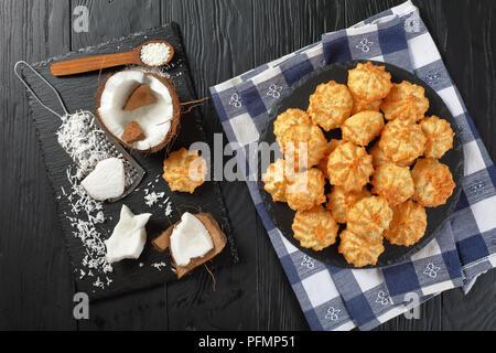 Deliziosa casa amaretti di cocco i cookie su una piastra su un tavoli in legno nero con ingredienti sul tagliere, vista orizzontale da sopra la piana Foto Stock