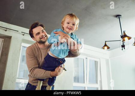 Il padre gioca con il suo figlio in un supereroe, un pilota in roo Foto Stock