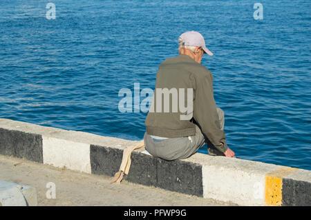... Un uomo anziano pescatore seduta su un parapetto in riva al mare e la  pesca su b2d81df9d51a