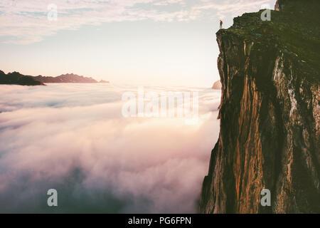 Traveler permanente sulla scogliera di bordo superiore di montagna sopra le nuvole al tramonto avventuroso viaggio lifestyle estate vacanze viaggio Foto Stock