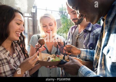 Happy amici condividendo cibo da asporto all'aperto Foto Stock