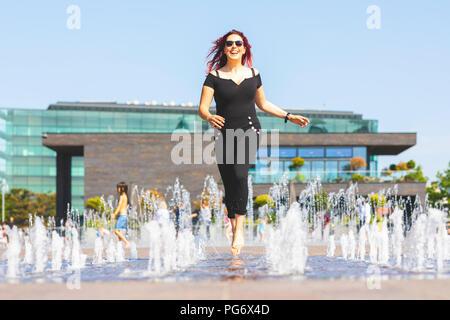 Giovane donna divertendosi in esecuzione attraverso una fontana Foto Stock