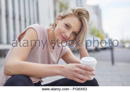 Ritratto di sorridere donna bionda con caffè da asporto nella città Foto Stock