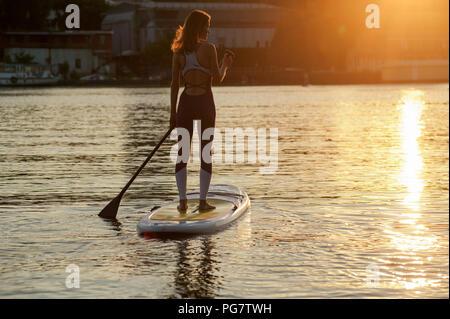 Stand Up Paddle board yoga eseguita da ragazza bella sulla città luminosa sullo sfondo, formazione yoga sulla spiaggia Foto Stock