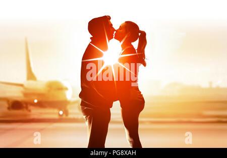 Coppia di giovani amanti in aeroporto e abbraccio bacio ogni altro Foto Stock