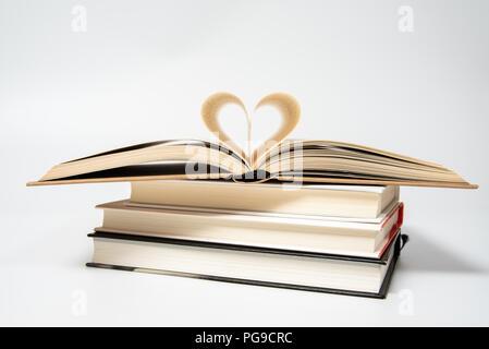 Close up del libro aperto con cuore sagomato da due pagine, isolati su sfondo bianco. Foto Stock