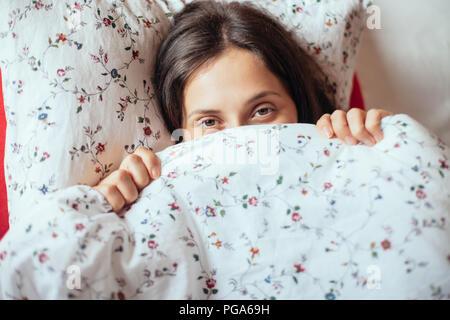 Giovane ragazza guarda sotto coperta nel suo letto, primo piano. Bella donna nascondendo la faccia Foto Stock