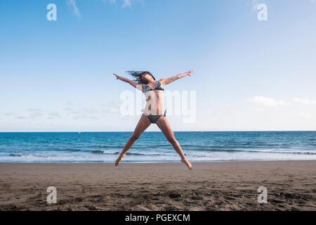 Bel corpo lifestyle fitness giovane donna jump pieno di felicità per la spiaggia vicino la riva e le onde dell'oceano blu. gioioso e divertimento estivo Foto Stock