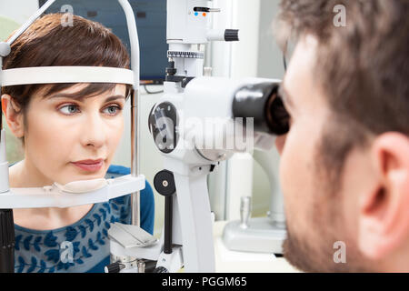 Bella donna avente un occhio esame con lampada a fessura / oculista di occhi clinic facendo un esame apparecchio con la visione del paziente mediante computer moderno Foto Stock