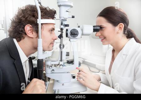 Un uomo avente un occhio test con lampada a fessura / medico donna in Oftalmologia Clinica facendo retina cornea diagnostica esame con la visione del paziente dalla moderna c Foto Stock