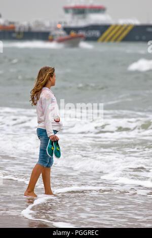 Giovane ragazza adolescente sta con i suoi piedi nudi in acqua e si affaccia sul mare Foto Stock
