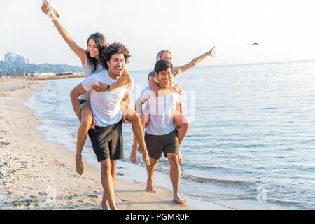 Gruppo di amici a piedi lungo la spiaggia, con gli uomini dando piggyback ride di amiche. Felice giovani amici godendo una giornata in spiaggia