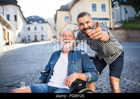 Un adulto hipster figlio con il suo anziano padre in sedia a rotelle su una passeggiata in città, che punta a qualcosa. Foto Stock