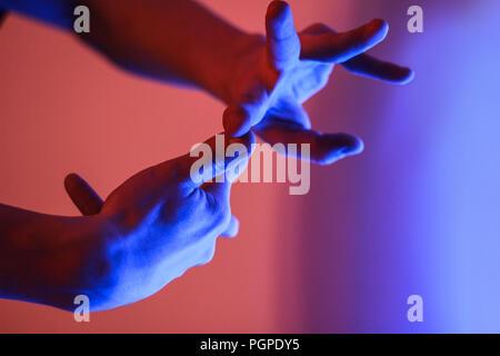 Le mani umane in colore rosso e blu neon luce fluorescente Foto Stock