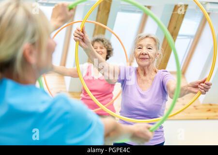 Gli anziani fare fitness training con il pneumatico nella fisioterapia Foto Stock